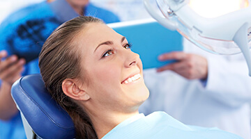 Smiling woman lying in dental chair with dental lamp shining on her