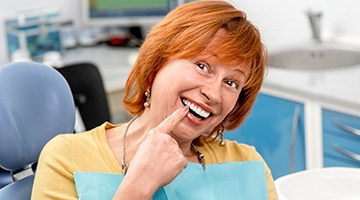 Senior woman I dental chair pointing to smile