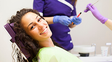 Dental assistant standing behind smiling young woman lying in dental chair