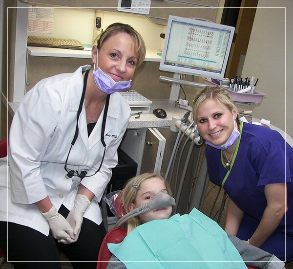 Dr. Guthrie and dental assistant treating a young girl