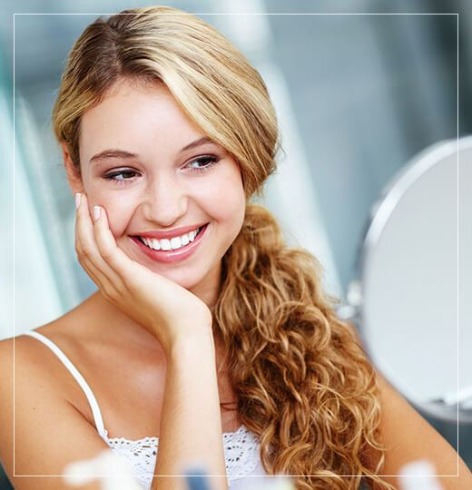 Smiling young woman touching her face