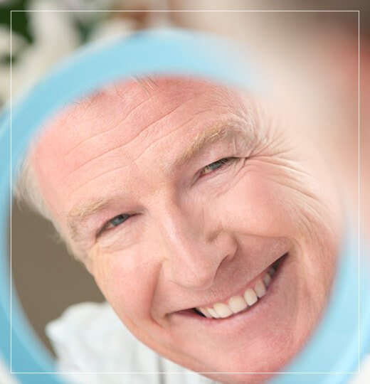 Smiling elderly man looking at his own face in a mirror