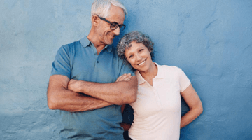 Portrait of a couple smiling in front of blue wall