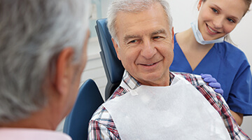 Dentist and dental assistant standing  next to elderly man in dental chair