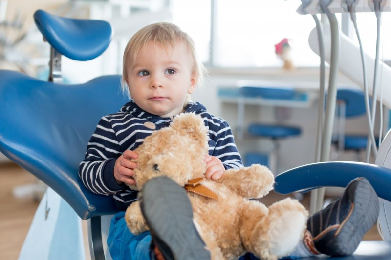 Toddler holding teddy bear at first dental visit